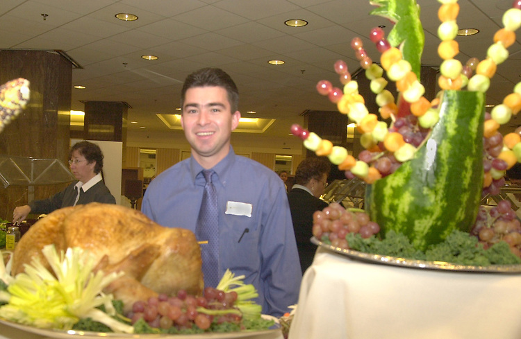 1turkey111501 -- Milton Salvador, a seven year employee of the Dirksen cafeteria smirks at the fruit turkey he constructed early Thursday morning, as the Senate prepares for a little Thanksgiving break.