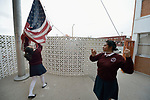 Students take down the U.S. flag at the Lydia Paterson Institute in El Paso, Texas, where most of the students cross the border every day from their homes in Juarez, Mexico, to study at the United Methodist-sponsored high school.