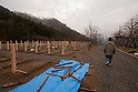 Onagawa, Japan - A photo made available on April 11 shows Yoshikatsu Hiratsuka, 66, walk to where his wife and mother rest in peace at a temporary mass grave for the March 11 earthquake and tsunami victims. Yoshikatsu was visiting a friend at the time the earthquake hit and he quickly rushed back home to later see his wife and mother in front of the house thinking how to escape. Before the two could react to a plan to escape, the 10-meter tsunami swept them away, leaving Yoshikatsu to live. His son is still missing and continues to search for him everyday. (Photo by Christopher Jue/AFLO) [2331] **ITALY OUT**