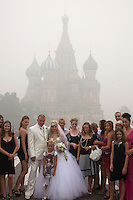 Moscow, Russia, 07/08/2010. .A wedding party poses for photographs in Red Square in the worst smog so far in the record high temperatures of the continuing heatwave. Peat and forest fires in the countryside surrounding Moscow have resulted in the Russian capital being blanketed in heavy smog.