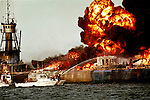 The US Coast Guard fights a fire on a barge carrying jet fuel, following a crash between a freighter and two barges, Aug. 10, 1993 in Tampa Bay FL.
