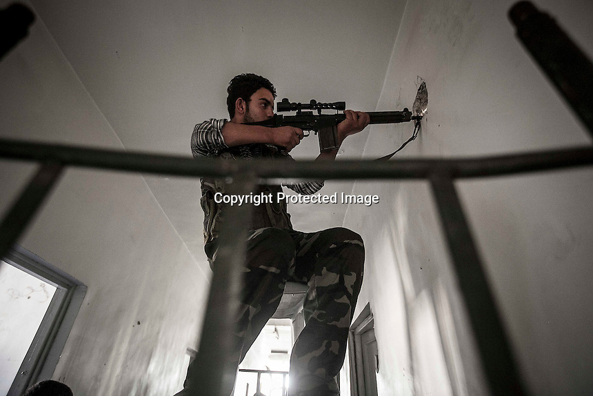In this Tuesday, Oct. 30, 2012 photo, a rebel sniper belonging to the Liwa Al-Fatah keeps an eye on his enemy position from a school building during skirmishes with the Syrian army in the nearby Bustan Al-Pasha front line in Aleppo, Syrian's largest city. (AP Photo/Narciso Contreras).