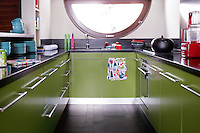 The small kitchen has vivid green units combined with a black work surface and floor