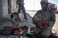 In this Wednesday, Sep. 25, 2013 photo, a Syrian opposition fighter sits accompanied by his son and daughter outside his home in the vicinity of Habit village, in the Syrian central province of Hama. (AP Photo)