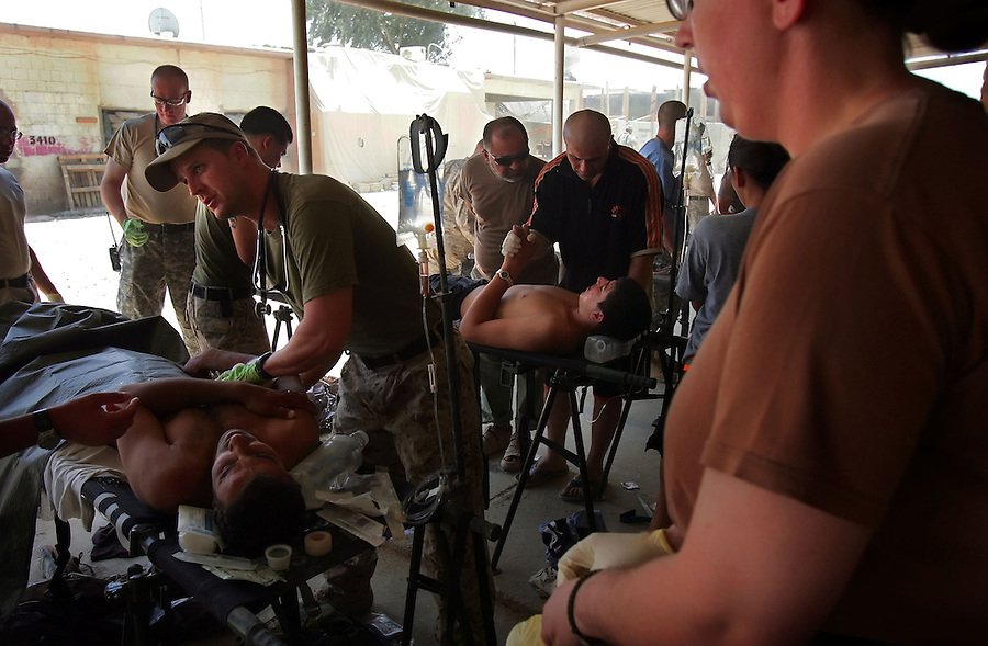 Army medics and Navy corpsmen at Ramadi Surgical - a joint Army-Naval surgical unit at Camp Ramadi - tend to Iraqi policemen and civilians wounded by a car bomb on Thursday August 10, 2006.