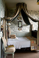 The master bedroom of the house is a symphony of grey with stripes, patchwork and toile de Jouy blending in a skilfully orchestrated combination