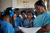Anjalakshi Krishnamurthy (age 10,  wearing beads) and her classmates wait for the attention of their teacher at the Government Girls High School, Venugopalapuram in Cuddalore. ..The five Krishnamurthy sisters from Pudupettai were placed in the Government Home for Tsunami Children in Cuddalore, Tamil Nadu when they lost their mother to the 2004 tsunami. Their father, Krishnamurthy, had decided he could no longer provide day-to-day care for his daughters. Krishnamurthy later remarried. The Krishnamurthy sisters now range in age from eight to sixteen...The four younger sisters are still at the Governement home (or orphanage). In summer 2009, Sivaranjini, the eldest aged sixteen, failed her 10th Standard exams and had to drop out of school so leaving her not eligible for care at the Government home. She is now living with her father and his new wife Nagamalli's house 30km away in Pudupettai. Krishnamurthy is intending that Sivaranjini marry a second cousin in 2010. ..Krishnamurthy visits the Government orphanage once a week to see his four younger daughters. Nagamalli is popular with all five sisters. She provides them attention when they are together and is genuinely interested in their well-being. Sivapriya remains close to her paternal aunt Kamasala with whom she used to live in the fishing village of Thazanguda. Kamasala visits Sivapriya at the orphanage every fortnight. The sisters return to their father's home for festivals including Diwali and the Pudupettai village temple festival...According to Revathi, the staff member in charge at the Government home, the absence of the elder Sivaranjini has had the effect of making the remaining four sisters still at the home increasingly independent. For instance, where they used to all sleep together the girls now sleep in different dormitories. The eldest of these four, fourteen year-old Sivapriya has adopted some of the responsibilities of her elder sisters including coordinating clothes washing and helping her younger s