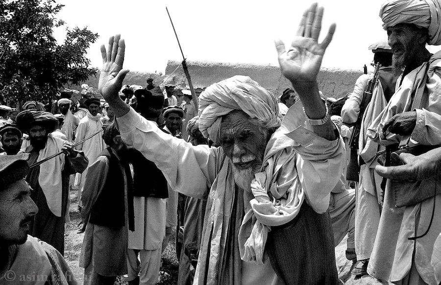 azam warsak, south waziristan, pakistan 2004: a man tries to stop a tribal lashkar from destroying his family home.  most homes have move than one family living within.  even the suspicion that one member had supported suspected al qaeda fighters means that the entire house is destroyed and all its inhabitants cast out.<br />