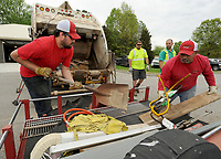 NWA Democrat-Gazette/ANDY SHUPE<br /> Tyrell Murphy (left), a worker with the city of Farmington Street Department, and Isaac Navarro (right), a worker with the city's Parks and Recreation Department, work together Friday, April 14, 2017, to unload a trailer of unwanted items into a truck as Waste Management driver James Minor (center) and lead driver Forrest Parker help during the first day of the city's Spring Cleanup behind the Farmington Fire Department fire station. With proof of city residency, citizens can drop off items from 7:30 a.m. to noon today free of charge. No household trash, hazardous waste, paint, oil, gas, tires, refrigerants or yard waste can be accepted. Boston Mountain Solid Waste district is also partnering to offer free electronic recycling.