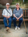 Two men with canes sit on a park bench near the Thracian Tomb, Kazanlak, Bulgaria