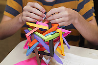 Aaron Pfitzenmaier folding a modular origami design between classes