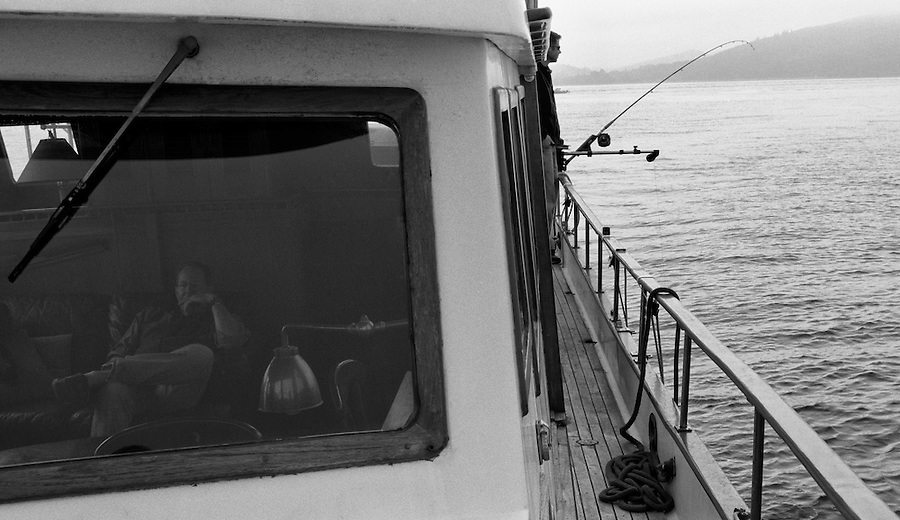 One man fishes while a middle-aged man rests inside his boat, a Puget Trawler.
