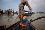 Mot, 17, fishes for smaller fish on the Hau Giang River, a tributary of the Mekong River, in Chau Doc, in the An Giang Province, Vietnam. When the Mekong River reaches Vietnam it splits into two smaller riveres. The &quot;Tien Giang&quot;, which means &quot;upper river&quot; and the &quot;Hau Giang&quot;, which means &quot;lower river&quot;. Photo taken on Monday, December 7, 2009. Kevin German / Luceo Images