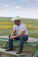 Cowboy sitting on a picnic table in a field