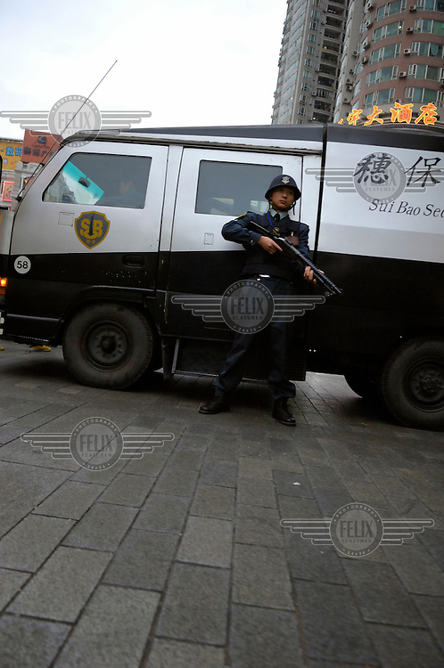 Armed guard for an armoured security van picking up money from a bank.