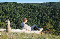 Girl looking down the hills covered with trees in Russian National Park