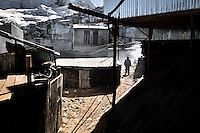 A miner walks along the corrugated metal shacks, homes of the gold miners, in La Rinconada, Peru, 5 August 2012. During the last decade, the rising price of the gold has attracted thousands of people to La Rinconada in the Peruvian Andes. At 5300 metres above sea level, nearly 50.000 people work in the gold mines and live in the nearby colonies without running water, sewage system or heating service. Although the work in the mines is very dangerous (falling rocks, poisonous gases and a shifting glacier), the majority of miners have no contract and operate under the cachorreo system - working 30 days without payment and taking the gold they supposedly find the 31st day as the only salary. In spite of a demaged environment, caused by mercury contamination from the mining and the lack of garbage disposal, people continue to flock to the region hoping to find their fortune.