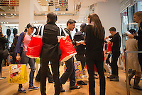 Customers receive an omiyage, a gift, upon leaving the grand opening of the Uniqlo Flagship store on Fifth Avenue in New York on Friday, October 14, 2011.  The store is a staggering 89,000 square feet on multiple levels and is Fast Retailing's second store in the United States with a third opening next week in the Herald Square shopping district. The largest store on Fifth Avenue filled to the brim with affordable clothing it competes with stalwarts such as the Gap and Zara which are in the immediate proximity. Fast Retailing plans on opening 200 to 300 stores worldwide until 2020 and currently has 1000 stores. (© Richard B. Levine)