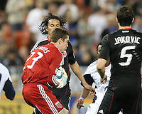 Troy Perkins #23 of D.C. United picks up the ball between Juan Manuel Pena #3 and Dejan Janovic #5 during an MLS match against the New England Revolution on April 3 2010, at RFK Stadium in Washington D.C.