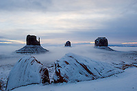 After fresh spring snow, fog rolls through the low-lying areas of the Monument Valley Navajo Tribal Park in southern Utah, at sunrise Saturday, March 11, 2006. The stunning vistas in the park, stars in many John Ford westerns, are an often-forgotten destination for American travelers. (Kevin Moloney for the New York Times)