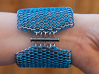 "A blue and silver dragonscale weave maille bracelet on  a wrist, focusing on the clasp.  It's made from saw cut 18 gauge 1/4"" ID blue anodized aluminum rings and saw cut 19 gauge 5/32"" ID bright aluminum rings.  The clasp is a gunmental plated slide clasp.   Handmade by Michelle."