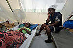 Paul Biberstend, 6, is treated for cholera in treatment center run by Oganizasyon Sante Popilè (OSAPO) Montrouis, Haiti. Cholera appeared on the quake-ravaged Caribbean island nation in late 2010. OSAPO's work is supported by Diakonie Katastrophenhilfe and the Lutheran World Federation, both members of the ACT Alliance. In addition to treating people infected with cholera, OSAPO sends teams of health educators into urban and rural communities to provide education, distribute anti-bacterial soap and oral rehydration salts, and refer sick patients back to the OSAPO clinic. Sitting alongside the patient is his mother, Odette...