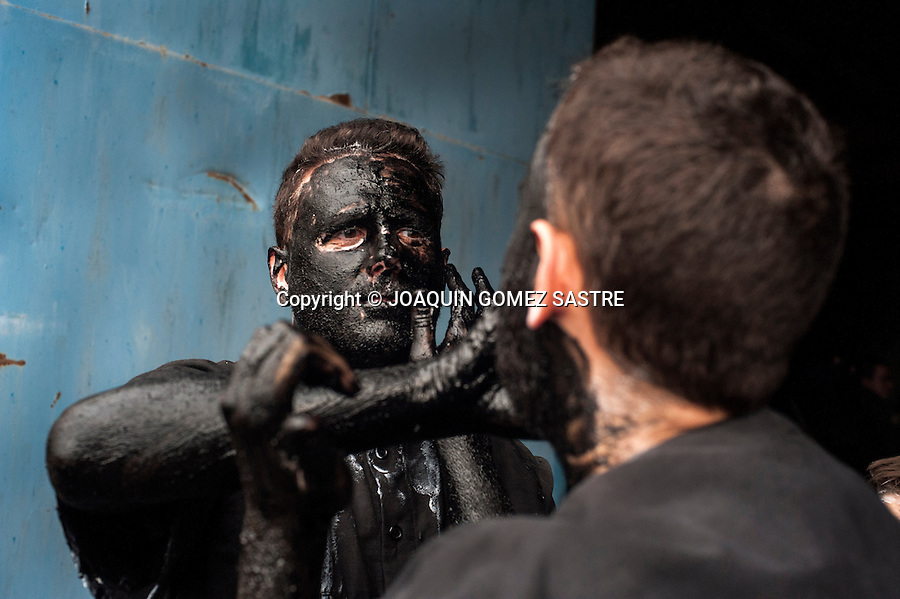 Two participants in the carnival Devils Luzon (Guadalajara) smear themselves with soot and tar for his costume devils.