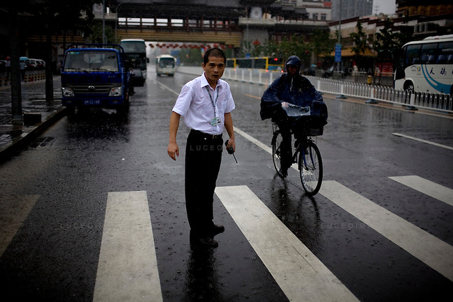 A parking attendant braves a down pour in Beijing, China on Thursday, August 14, 2008.  Kevin German