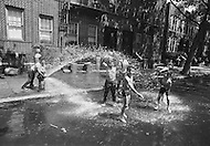 Brooklyn, New York City, NY. August, 1971. <br /> The long, hot summer of August 1971 exacerbated tensions in the black ghetto of  New York. Poor housing, poverty, unemployment and crime did not facilitate the poor inhabitants during the heatwave. Children play with a water hydrant - a classic New York summer scene.