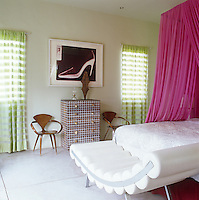 The juxtaposition of a vivid pink bed canopy and contrasting green and white checked curtains results in a fresh and bright feel to this bedroom