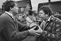 Two men hold onto one of the 'bottles' or kegs fought over during the traditional bottle kicking and hare pie scramble on Easter Monday in Hallaton Village, Leicestershire.
