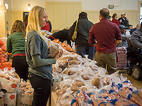 "Volunteers distribute turkeys, stuffing and all the other ""fixin's"" for a Thanksgiving dinner to the neediest at the Catholic Charities' Lt. Joseph P. Kennedy Center in Harlem in New York on Tuesday, November 25, 2014. The families, who would otherwise not be able to afford the dinner, received the donations during a time where sources of relief for the poor and unemployed are constrained if not terminated. The food is from the generosity of the former baseball player Rusty Staub and the Urso Fund for the Hungry and Homeless. (© Richard B. Levine)"