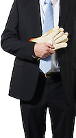 businessman ready to put on some gloves to do the dirty work