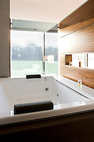 A large jacuzzi measuring two metres square has been positioned in front of a window of one-way glass affording panoramic views of surrounding woodland