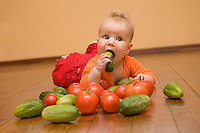 Five month old caucasian baby on wooden floor and eating pickle. Floorboard. Vegetables.