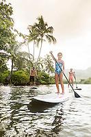 A young girl enjoys a family SUP lesson on the Wailua River, Kaua'i.