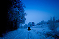 Lone walker in traditional snow scene in The Cotswolds, Swinbrook, Oxfordshire, United Kingdom