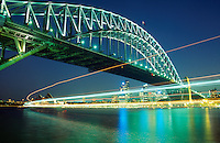 The lights of a ferry pass under the harbor bridge to Milsons Point, Sydney,Australia