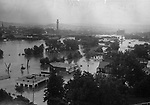 Panoramic view of Waterbury taken from the Waterbury Hospital grounds when flood waters were at their height. The Stop & Save market is in the foreground, railroad station tower in the background. The parallel lines of trees in the center flank the sides of the river when not at flood stage.