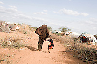 Kenya - Dadaab – 21st July 2011. A Somali mother and her little girl walking throught Dagahali camp hand in hand.