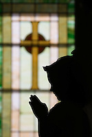A young girl stands with her hands raised in prayer in front of a stained glass window after her first communion sacrament at a Catholic church in Johnstown, OH.<br />