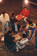 May 7th, 1987. In Melilla, Spanish Morocco. Outside, in Plaza Mercado del Polygono, muslims people playing cards after the Ramadan dinner.