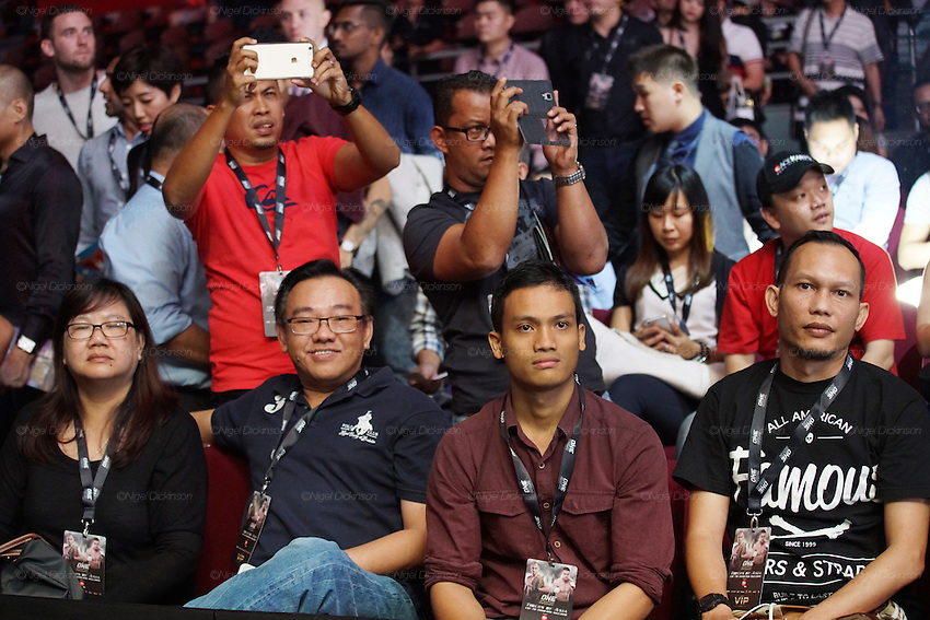 Spectators filming with their digital equipment whilst watching the MMA cage fighting<br /><br />MMA. Mixed Martial Arts &quot;Tigers of Asia&quot; cage fighting competition. Top professional male and female fighters from across Asia, Russia, Australia, Malaysia, Japan and the Philippines come together to fight. This tournament takes place in front of a ten thousand strong crowd of supporters in Pelaing Stadium. Kuala Lumpur, Malaysia. October 2015
