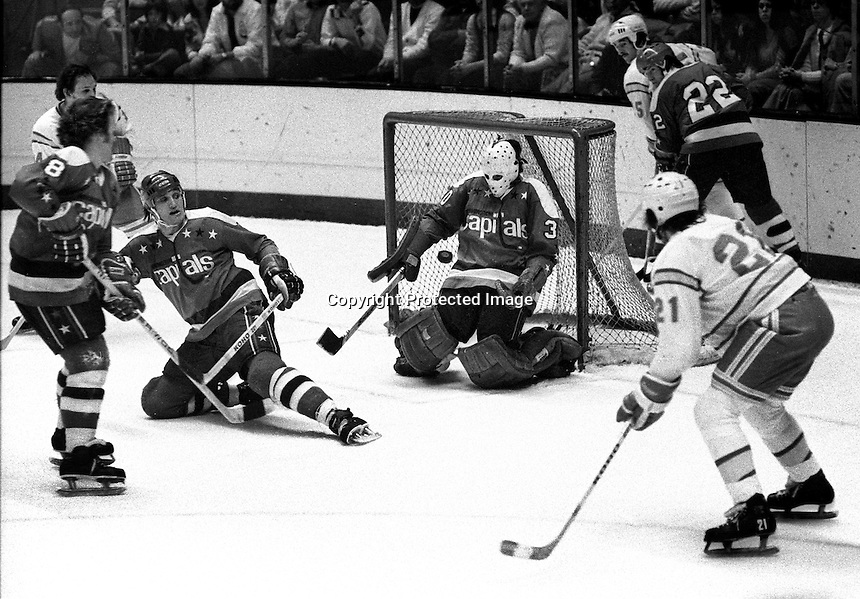 California Golden Seals vs Washington Capitols. goalie Bernie Wolfe blocks shot, from Dennis Maruk, Jack Lynch and Don McLean. (1975 photo/Ron Riesterer)