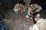 U.S. Army 101st Airborne 3rd Battallion 502nd Infantry soldiers plan a night time raid in the Northern Iraqi city of Mosul using packaged meals, kleenex packets, and boxes of soap to represent the layout of their target neighborhood and the position of their vehicles.