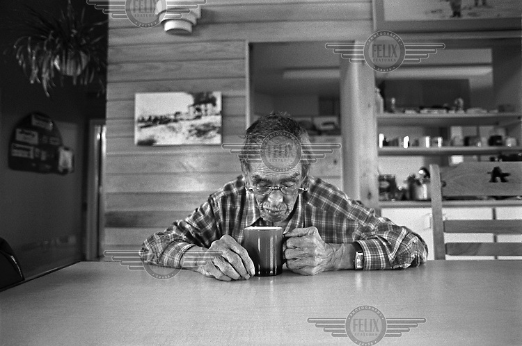 Johnny Kautjasiak, an elderly Inuit, drinks a cup of coffee during a visit to his family's home in Kuujjuaq.
