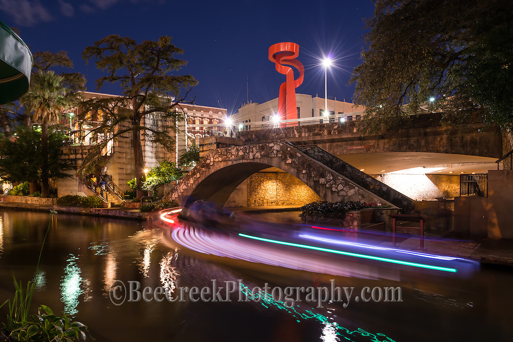 We took this cityscape of the San Antonio river walk at night with the boat trail from the tourist boats as they go in and out from under this pedestrian bridge that sit under the Torch of Friendship.  We like the light trails they created so we took a few shots. Watermark will not appear on image