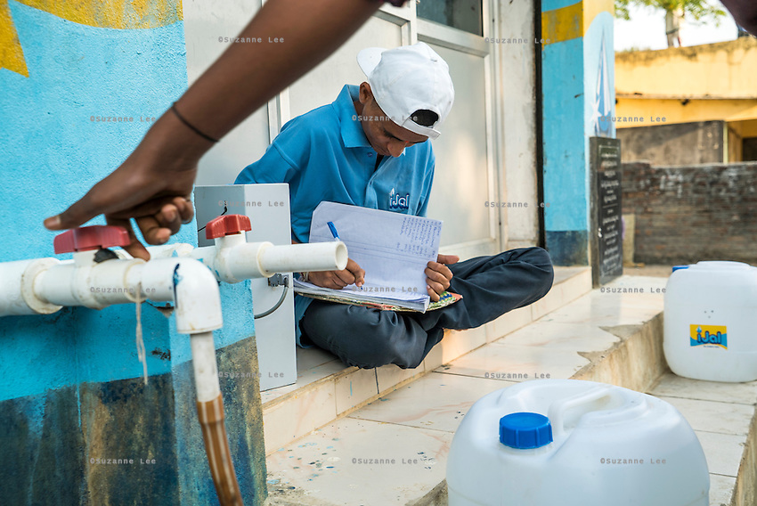 The station operator records his daily sales in a book at the iJal station in Peddapur, a remote village in Warangal, Telangana, India, on 22nd March 2015. Safe Water Network works with local communities that live beyond the water pipeline to establish sustainable and reliable water treatment stations within their villages to provide potable and safe water to the communities at a nominal cost. Photo by Suzanne Lee/Panos Pictures for Safe Water Network
