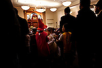 Los Angeles, California, March 19, 2011 - Children dressed in costume mix with adults during the reading of the Megillah during the Jewish holiday Purim at the Nessah Synagogue in Beverly Hills. The synagogue is home to a predominently Persian congregation. ..Purim is a Jewish holiday that commemorates the deliverance of the Jewish people living in the Persian Empire from genocide at the hands of the political advisor, Haman, to the Persian King Ahasuerus, as documented in the Talmud's Book of Esther. It is celebrated by the reading of the Scroll of Esther or the Megillah, sending food gifts to friends, giving charity to the poor and celebrating with a festive meal. During the reading of the Megillah, when Haman's name is mentioned (which happens 54 times) the congregation engages in loud roars and the use of rattles in an effort to blot out his name. Today children and some adults dress in costume and masquerade to celebrate Purim. The custom is believed to have originated during the 15th century by Italian Jews influenced by the Roman carnival. One idea for the costumes is that God disguised his presence behind many of the natural events that happened during Purim. .