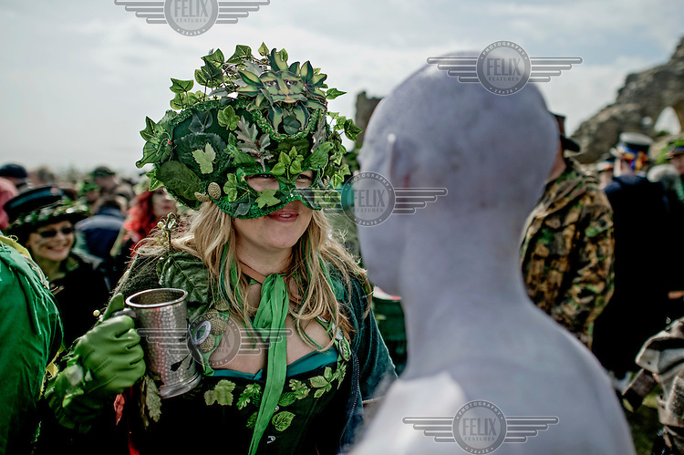 A woman holding a tankard speaks to a man painted white at a Jack in the Green Festival. <br /> The festival is part of a recent revival of an older custom where people would wear frameworks covering much of their bodies which were decked out in foliage. The custom is connected to English May Day parades that herald  the coming of summer.